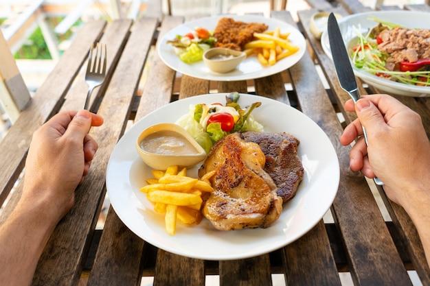 Visão em primeira pessoa de um cara que come comida em um café de verão.