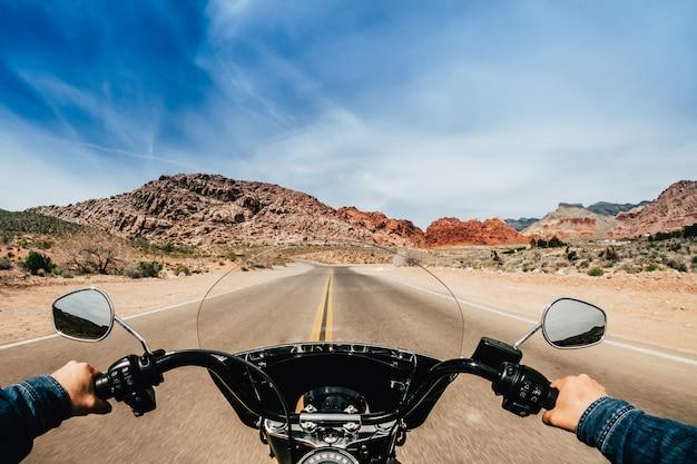 Visão em primeira pessoa de um homem dirigindo uma motocicleta em uma estrada