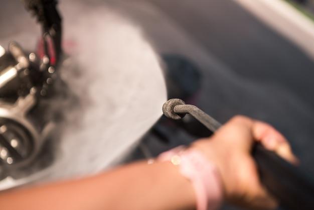 Visão em primeira pessoa de uma mulher limpando uma motocicleta com água pressurizada