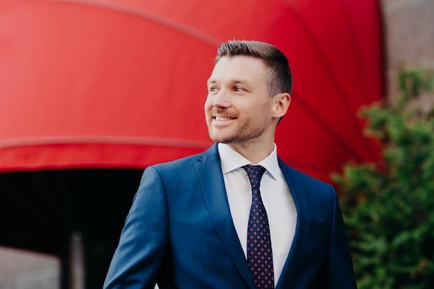 Visão externa do belo jovem empresário masculino em roupa formal