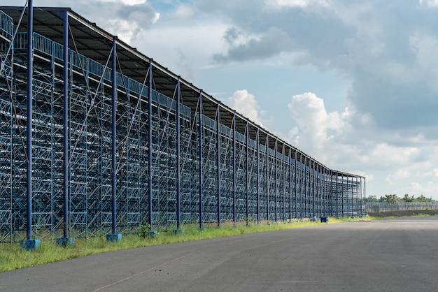 Visão externa do grande estádio em construção com estrutura de aço azul