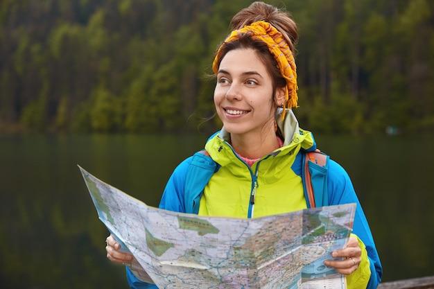 Visão externa horizontal do viajante satisfeito, verifica a rota no mapa de localização e explora um novo lugar