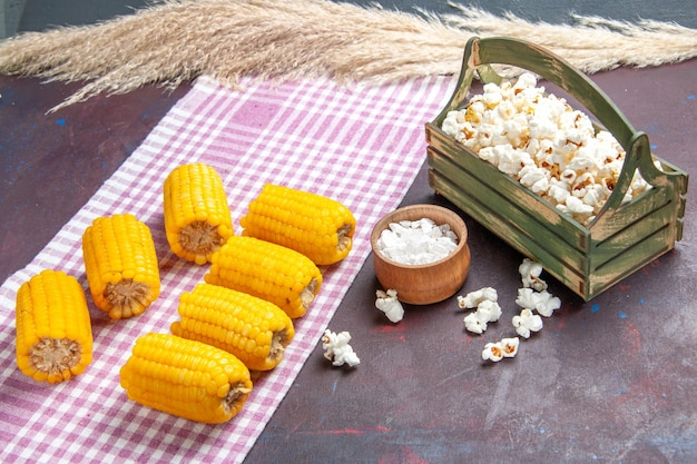 Visão frontal de grãos amarelos fatiados crus e frescos com pipoca em uma superfície escura alimentos vegetais de milho crus frescos