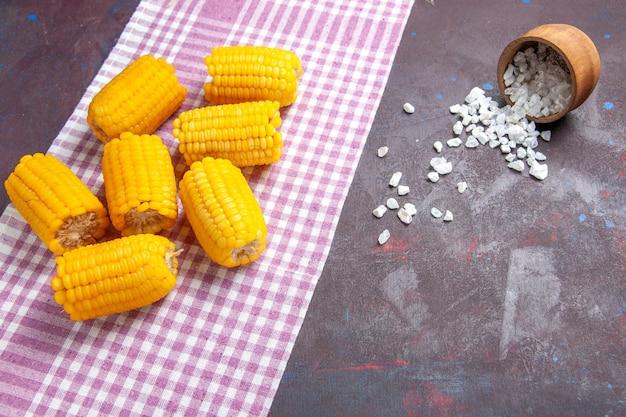 Visão frontal de grãos amarelos fatiados crus e frescos na superfície escura alimentos vegetais de milho crus frescos