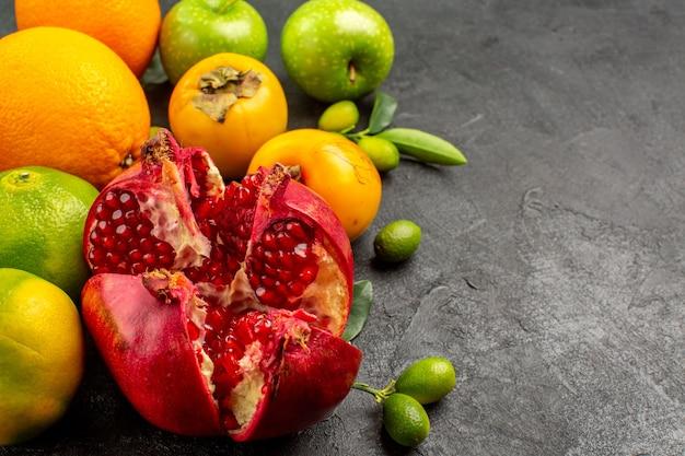 Visão frontal de romãs frescas com maçãs e outras frutas na superfície escura de frutas maduras