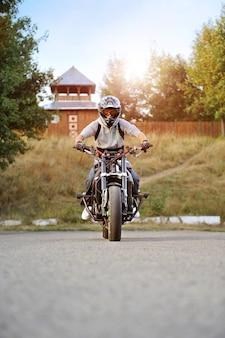 Visão frontal de um jovem motociclista forte andando em uma motocicleta esportiva