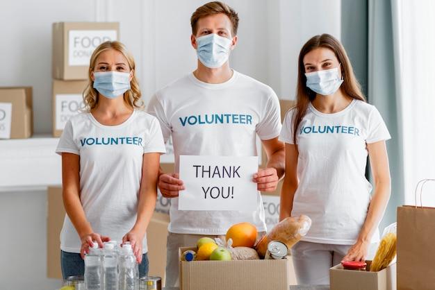Visão frontal de voluntários agradecendo por doar para o dia da comida