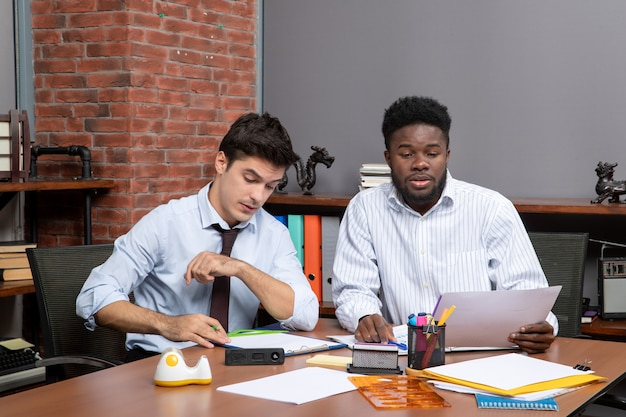 Visão frontal do processo de trabalho de dois empresários em trajes formais trabalhando no escritório
