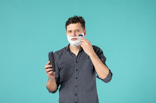 Visão frontal jovem homem barbeando o rosto com navalha no fundo azul