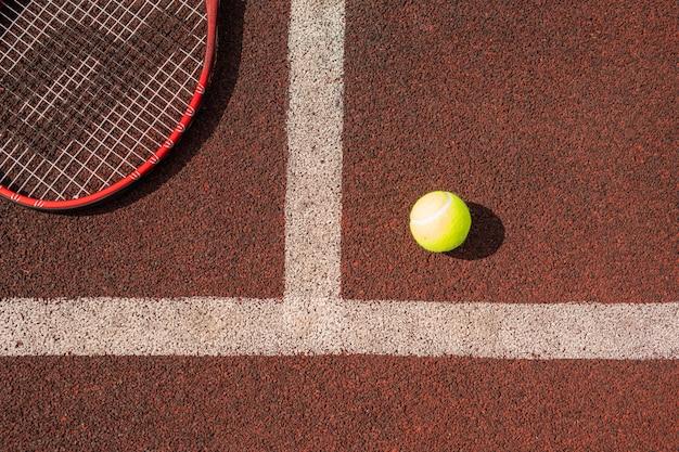 Visão geral da bola de tênis e parte da raquete no playground por linha branca