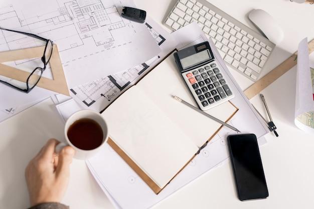 Visão geral da mão do engenheiro com uma xícara de chá preto ou café na mesa durante o trabalho sobre cálculos para esboço ou projeto