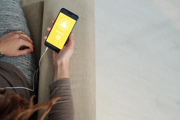 Visão geral da mão humana segurando um smartphone enquanto assiste a uma sessão de vídeo do curso de ioga
