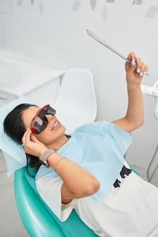 Visão geral da prevenção da cárie dentária. mulher na cadeira do dentista durante um procedimento odontológico.
