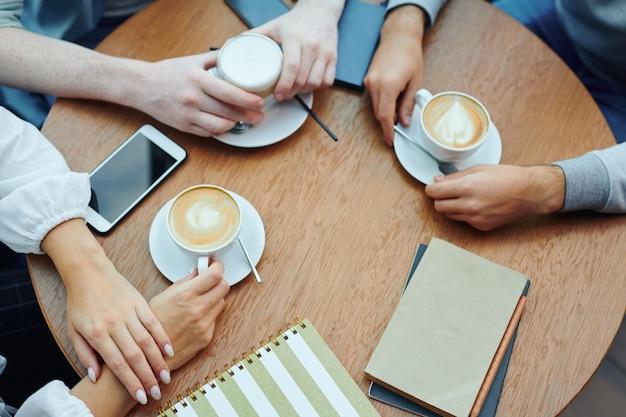 Visão geral das mãos de estudantes universitários com gadgets e bebidas reunidos à mesa no café para uma xícara de cappuccino e bate-papo