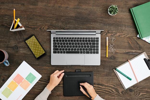 Visão geral das mãos do designer criativo contemporâneo sentado à mesa de madeira em frente ao laptop e usando uma caneta e um tablet gráfico
