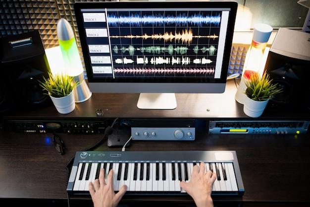 Visão geral das mãos do músico sobre o teclado do piano e a tela do computador com visualização do som da forma de onda na frente dele