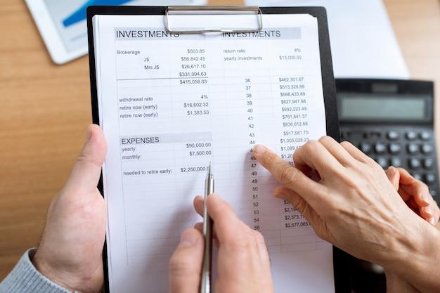 Visão geral das mãos humanas sobre papéis financeiros durante a discussão de despesas e investimentos