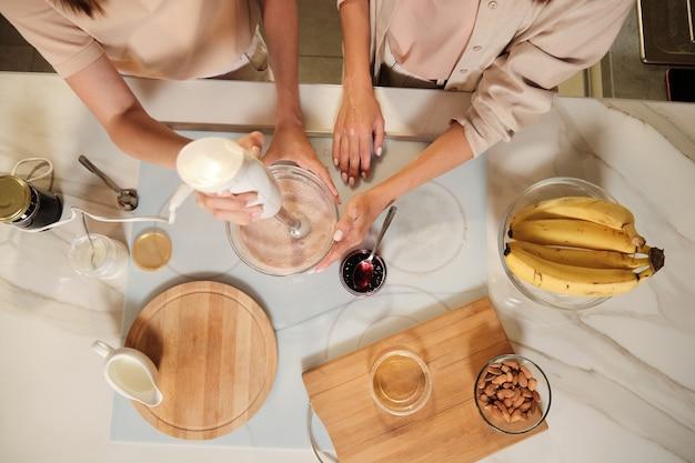 Visão geral de duas mulheres contemporâneas em pé junto à mesa da cozinha, misturando ingredientes de sorvete caseiro com uma batedeira elétrica
