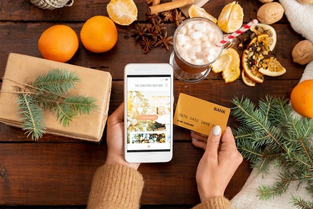 Visão geral de mãos humanas com smartphone e cartão de crédito cercadas por objetos de natal sobre uma mesa de madeira