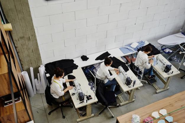 Visão geral de três alfaiates sentados perto de máquinas de costura elétricas em mesas durante o trabalho na nova coleção de moda na oficina