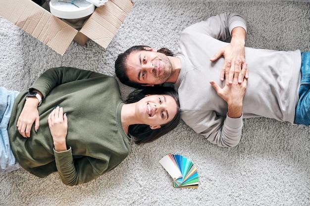 Visão geral de um jovem casal contemporâneo e alegre em trajes casuais, deitado no chão em sua nova casa ou apartamento