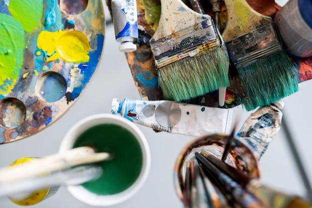 Visão geral de vários tipos de pincéis de mesa e em copos, tintas a óleo e paleta com cores misturadas
