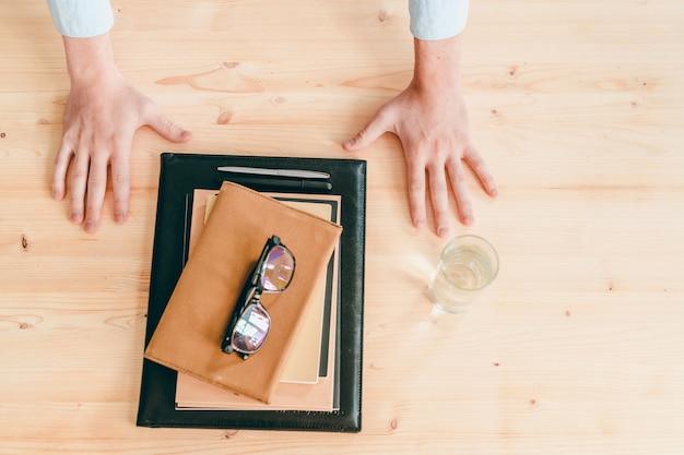 Visão geral do empresário entrega a mesa de madeira com um copo d'água e uma pilha de cadernos e canetas com óculos em cima