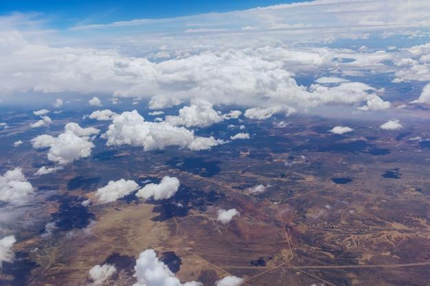 Visão geral no avião de nuvens fofas na paisagem cênica do deserto montanhoso do novo méxico com a cordilheira