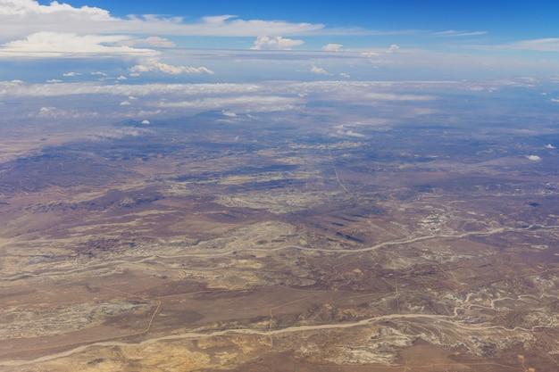 Visão geral no deserto do novo méxico do avião de nuvens fofas nas montanhas um avião