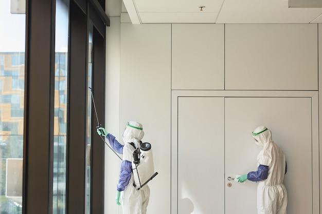 Visão gráfica de grande angular em dois trabalhadores de saneamento vestindo macacões anti-perigo, desinfetando o escritório,
