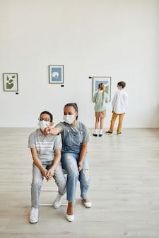 Visão grande angular de um menino e uma menina afro-americanos olhando pinturas na galeria de arte e usando máscaras, copie o espaço