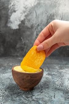 Visão horizontal da mão segurando a batata frita em uma tigela de maionese pequena na mesa cinza