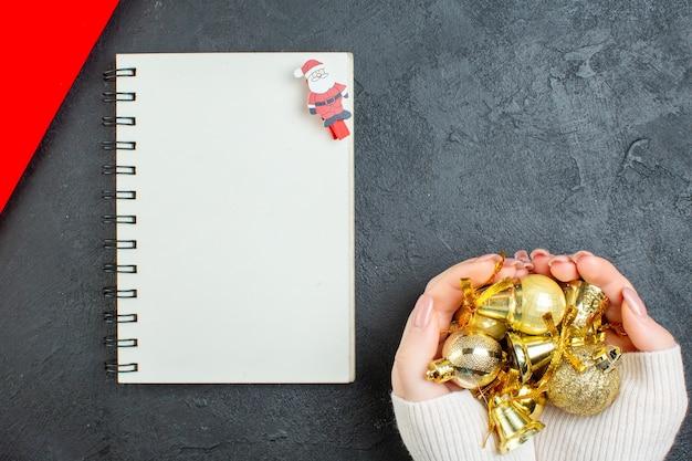 Visão horizontal da mão segurando acessórios de decoração e caderno em fundo escuro