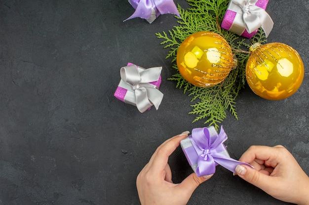 Visão horizontal da mão segurando um dos presentes coloridos e acessórios de decoração em fundo escuro