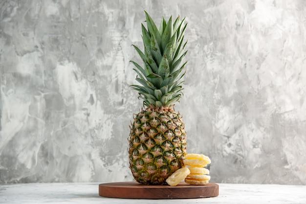 Visão horizontal de abacaxi dourado fresco inteiro e limas na tábua de pé na mesa branca