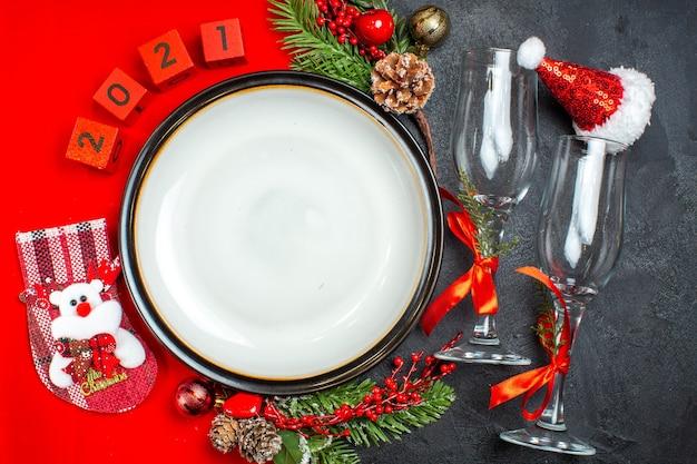 Visão horizontal de acessórios de decoração de pratos de jantar ramos de abeto xsmas meia taças de vidro na mesa escura