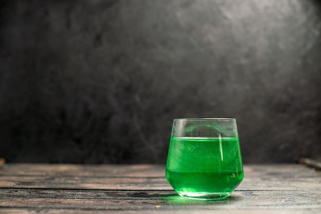 Visão horizontal de água verde em um copo deitado sobre fundo escuro