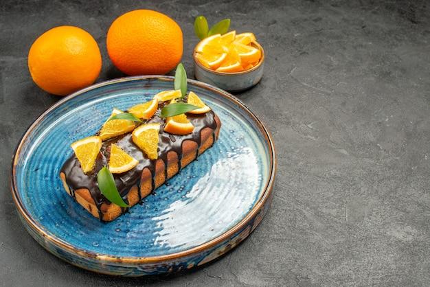 Visão horizontal de bolo delicioso e macio na bandeja e limão na mesa preta