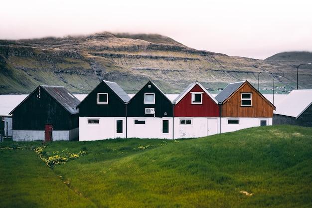 Visão horizontal de casas de fazenda coloridas na costa em terreno de grama verde