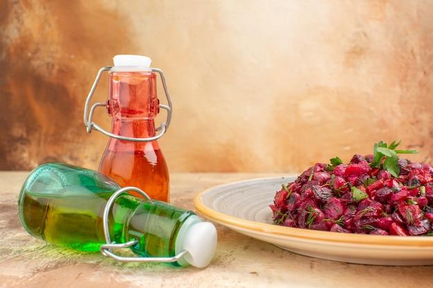Visão horizontal de deliciosa salada com beterraba e feijão e duas garrafas de óleo caídas em fundo de cor mista