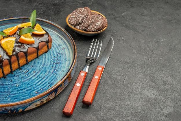 Visão horizontal de deliciosos bolos e biscoitos com garfo e faca na mesa preta