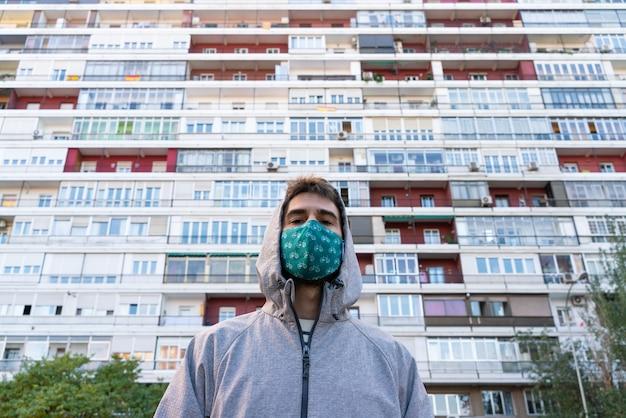 Visão horizontal de jovem usando uma máscara facial na frente de pequenos apartamentos baratos.