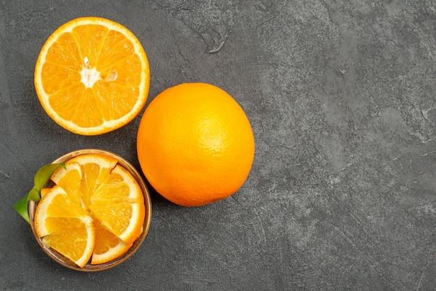 Visão horizontal de limões frescos inteiros e picados na mesa escura Foto gratuita