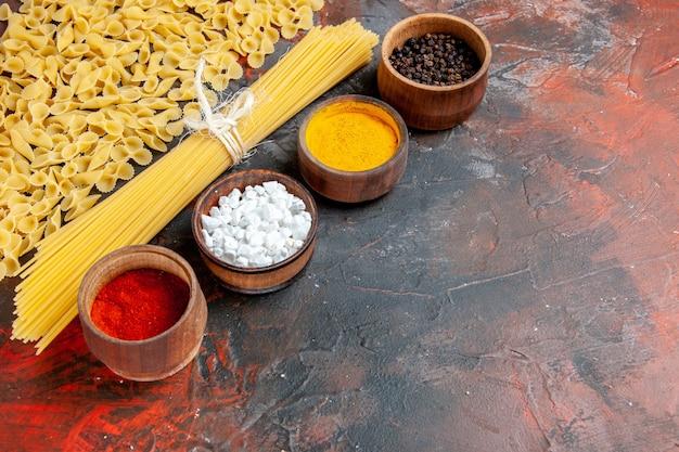 Visão horizontal de massas não cozidas em várias formas e diferentes temperos na mesa preta