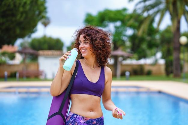Visão horizontal de mulher de cabelo encaracolado vestida com uma roupa de ioga, segurando água potável. estilo de vida de hidratação e fitness. exercício e hábitos esportivos saudáveis no verão.