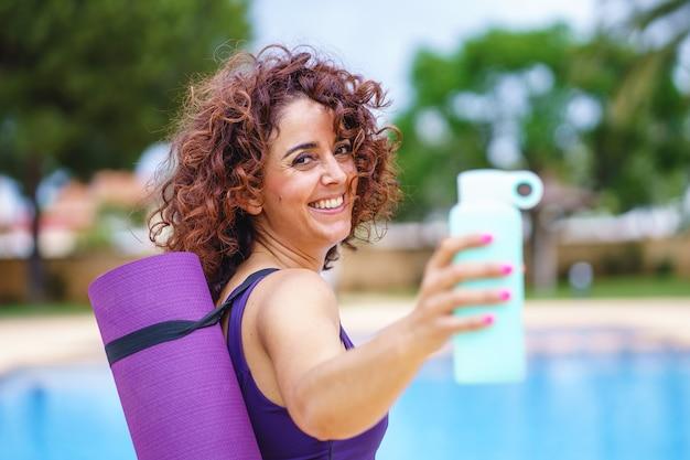 Visão horizontal de mulher de cabelo encaracolado vestida com uma roupa de ioga, segurando uma garrafa de água. estilo de vida de hidratação e fitness. exercício e hábitos esportivos saudáveis no verão.