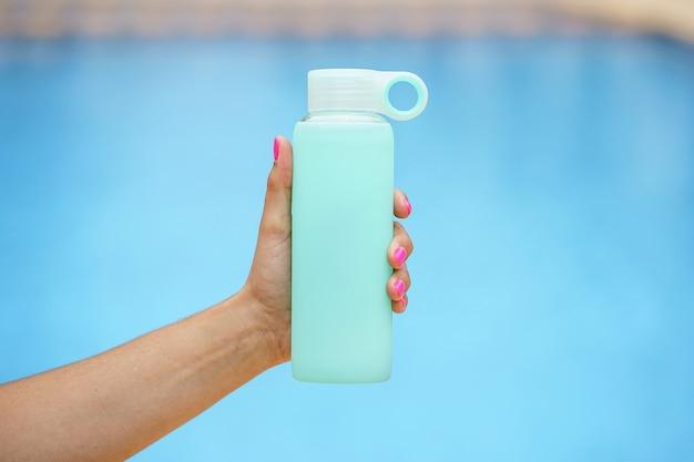 Visão horizontal de mulher irreconhecível pegando uma garrafa de água fria. estilo de vida de hidratação e fitness. exercício e hábitos esportivos saudáveis no verão.