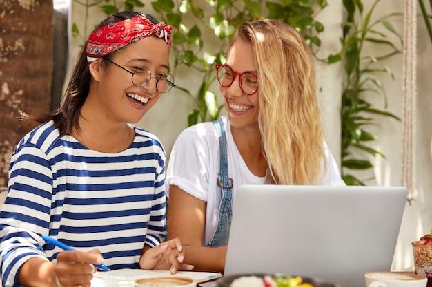 Visão horizontal de mulheres alegres, mestiças, escrevem artigo sobre empregos distantes, aprendem línguas pela internet