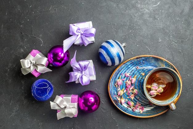 Visão horizontal de presentes coloridos e acessórios de decoração, uma xícara de chá preto sobre fundo preto