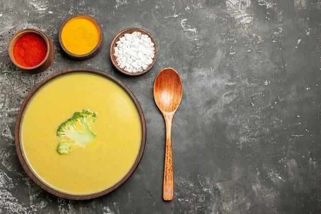 Visão horizontal de sopa cremosa de brócolis em uma tigela marrom com especiarias diferentes e colher na mesa cinza